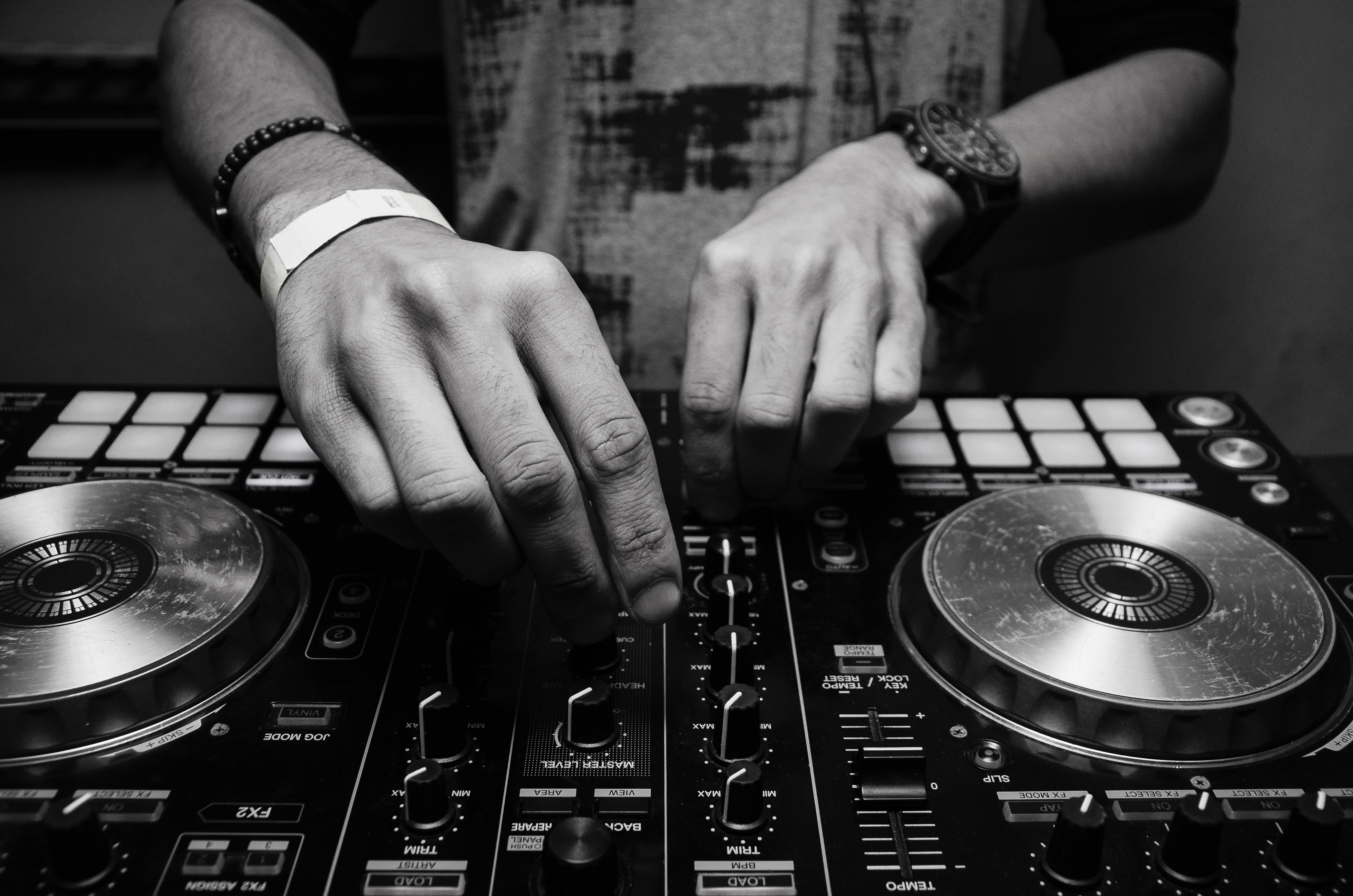 grayscale-photography-of-person-using-dj-controller-860707