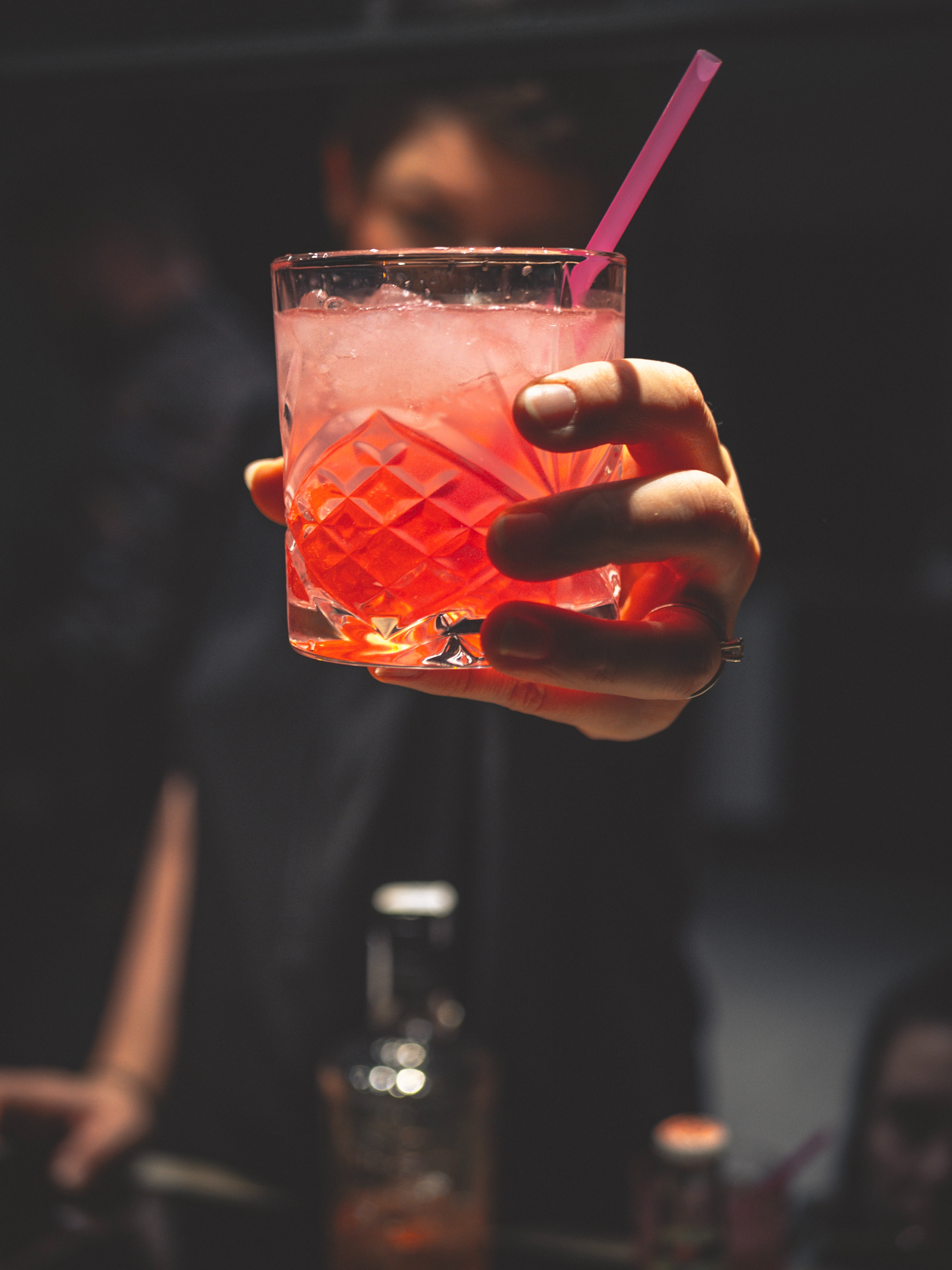 man-holding-forward-a-glass-of-iced-pinkish-colored-cocktail-3417441